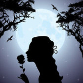 Silhouette of a girl with a flower under tree