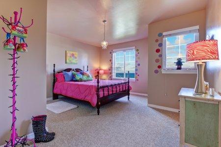 Girls pink bed in a beige large kids bedroom