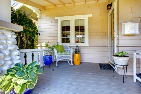 Covered entrance porch with plants and chair.