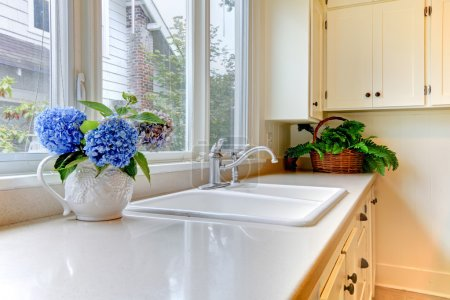 Kitchen sink with white cabinets and flowers.