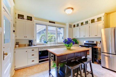 Photo pour Belle cuisine avec armoires blanches et îlot noir . - image libre de droit