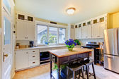 White antique remodeled kitchen with black island.