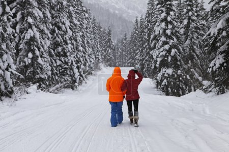Couple walking mountain winter snow covered road.