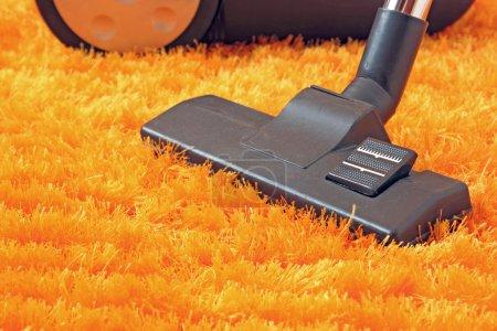 Photo pour Aspirateur moderne gros plan sur tapis orange - image libre de droit
