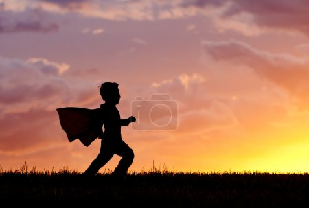 A young boy wearing a cape plays a super hero at s...