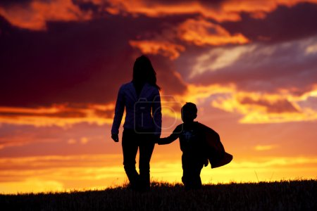 Photo for A tender moment of a mom and her son walking along at sunset. - Royalty Free Image