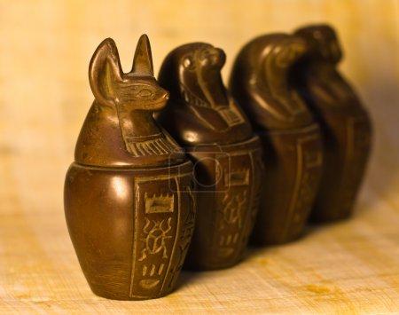 Photo pour Pots canopes utilisés par les Egyptiens sur le processus de momification pour stocker les viscères de leur propriétaire pour l'au-delà. Fond papyrus, profondeur de champ sélective . - image libre de droit