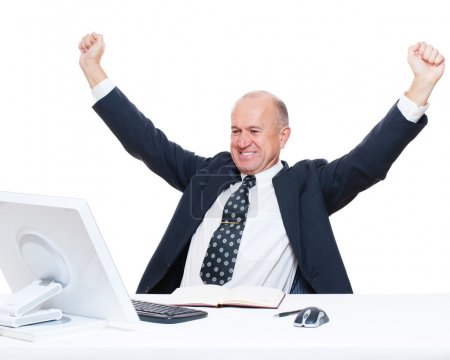 Senior happy businessman sitting in workplace