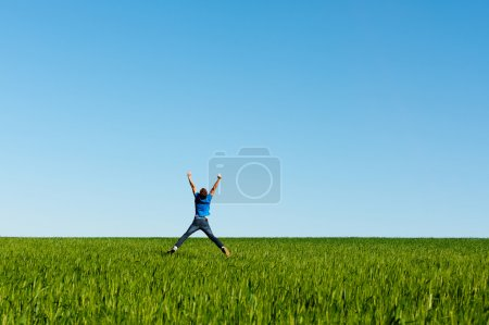 Man jumping on the green field over blue sky