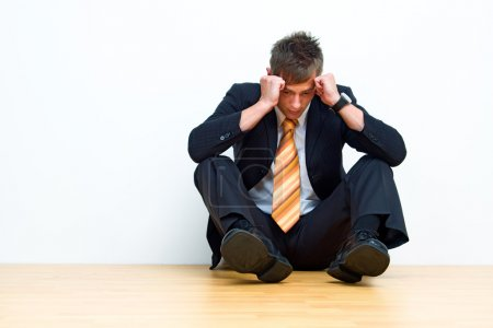 Photo for Unhappy businessman sitting on floor - Royalty Free Image