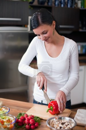 Young woman making vegetable salad