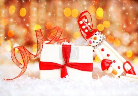 Foto de Holiday background with cute snowman Christmas tree decorative ornament & gift box in snow over abstract defocus lights - Imagen libre de derechos