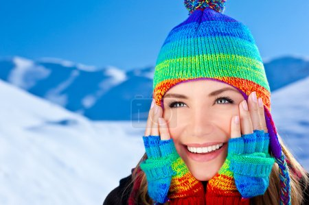 Photo for Happy smiling girl wearing colorful hat, beautiful female close up portrait, young pretty woman face over snow mountains blue background, winter fun outdoor, ha - Royalty Free Image