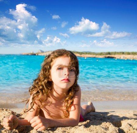 Beautiful little girl in sandy beach of Ibiza