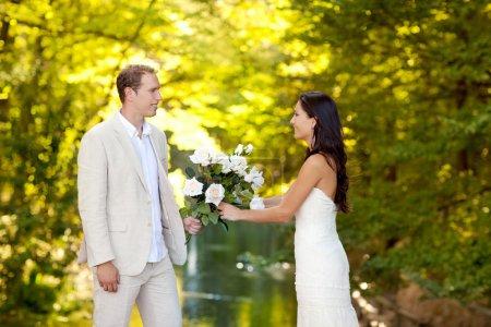 Photo pour Couple amoureux de bouquet de roses blanches en automne parc de rivière en plein air - image libre de droit