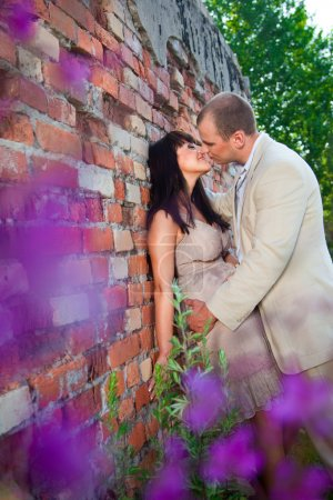 Romantic kiss near old brick wall