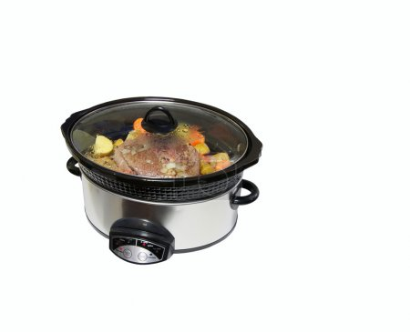 Photo for Nice image of a lightly browned seasoned blade roast with golden potatoes and chopped carrots simmering in a crock pot isolated on white with copy space. - Royalty Free Image