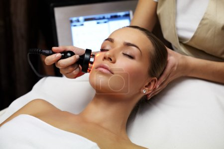 Photo for Woman lies on a table in a beauty spa getting a treatment - Royalty Free Image