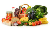 Abarrotes en cesta de mimbre, incluyendo frutas y verduras