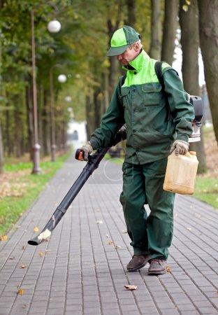 Photo pour Ventilateur de feuilles d'essence de fonctionnement d'paysagiste tout en nettoyant les pistes dans le parc - image libre de droit