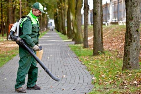 Photo pour Paysagiste, enlever les feuilles mortes dans le parc à l'aide de souffleur de feuilles essence - image libre de droit
