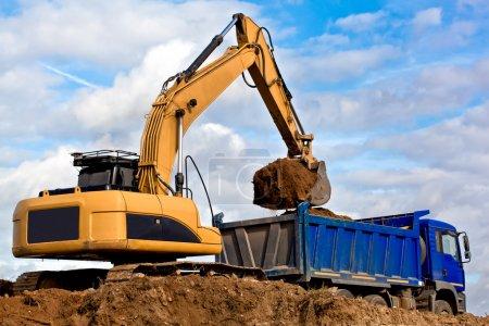 Photo pour Excavatrice chargeant un camion à benne dans une carrière - image libre de droit