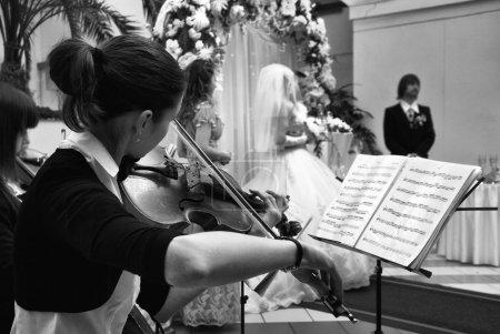 Photo pour Photo noir et blanc de fille joue du violon lors de la cérémonie de mariage - image libre de droit