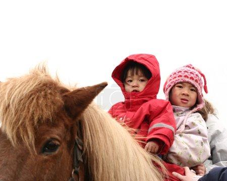 Photo pour Deux enfants sur un cheval en hiver - image libre de droit