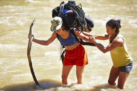 Rock climbing team crossing a river.