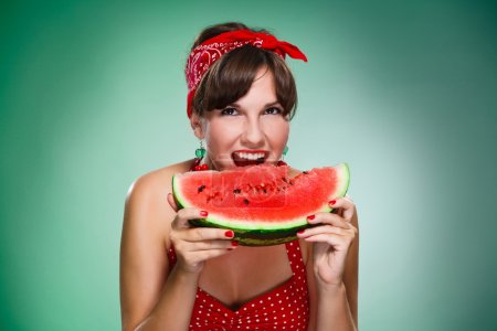 Photo for Happy girl bitten by a watermelon, isolated green background. - Royalty Free Image