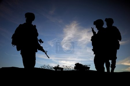 Silhouette of modern soldiers against sunset wky with military v