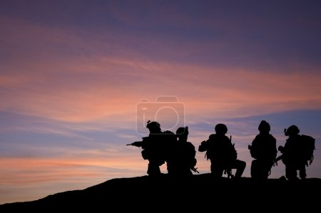 Photo for Modern troops silhouette against sunset sky in Middle East - Royalty Free Image