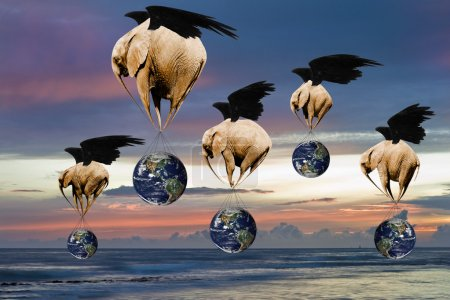 Creative concept image of flying elephants carrying Planet Earth