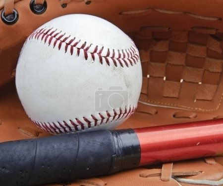 Close up of baseball in catcher's mittt with bat and shallow dep