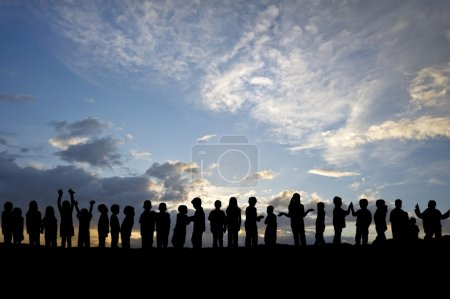 Silhouette of long line of children messing around against beaut