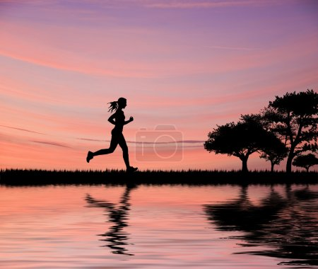 Female jogger silhouette against stunning colorful sunset sky an
