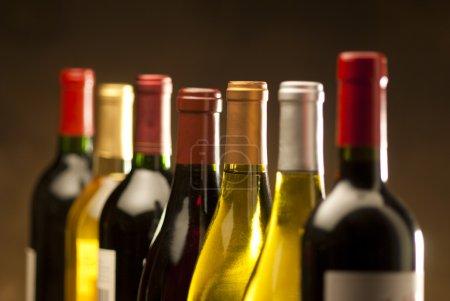 Photo pour Bouteilles de vin dans une rangée avec une profondeur de champ limitée - image libre de droit