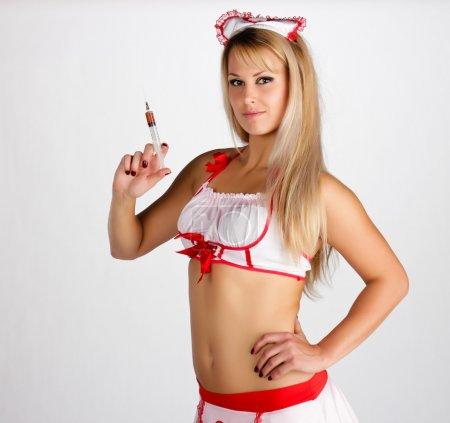 Photo pour Jeune femme en tenue d'infirmière avec une seringue - image libre de droit