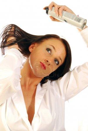 Photo pour Une femme se peignait les cheveux et mettait de la laque dans mes cheveux - image libre de droit