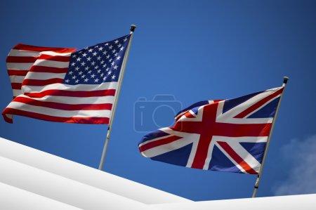Photo pour Drapeau anglais et américains dans le vent sur le ciel bleu - Etats-Unis et Royaume-Uni - image libre de droit