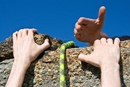 Rock climber reaching for helping-hand partner.