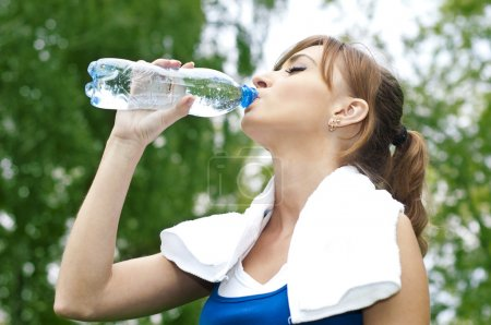 Photo for Young woman drinking water after exercise, summer park background - Royalty Free Image