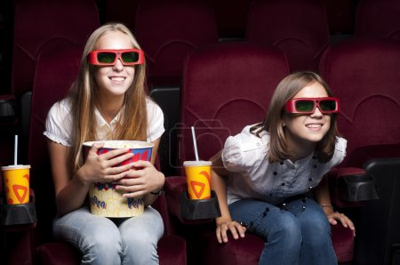 Photo for Two girls look three-dimensional cinema, sitting in the glasses, eat popcorn, drink drink - Royalty Free Image