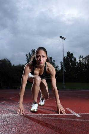 Photo for Starting position crouch by fit young female athlete on athletics running track, wearing black lycra sports outfit and running spikes. - Royalty Free Image