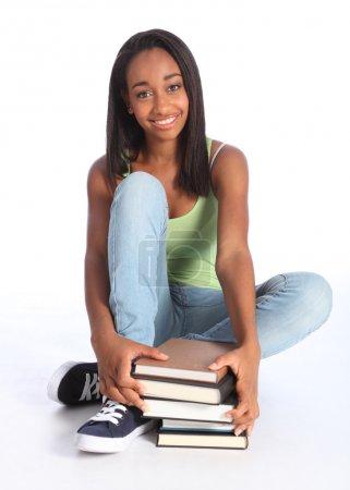 Photo pour Temps d'éducation pour une jolie jeune étudiante afro-américaine adolescente avec un grand beau sourire, assise sur le sol portant un jean bleu et un gilet . - image libre de droit