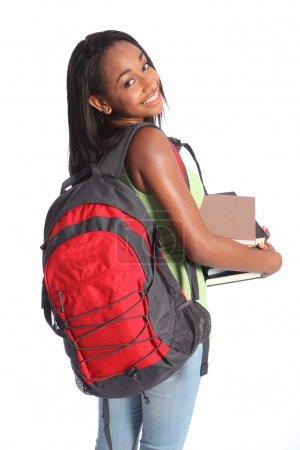 Photo pour Temps pour l'éducation de jolie jeune adolescente afro-américaine lycéenne avec un grand beau sourire portant un sac à dos rouge et tenant des livres d'étude . - image libre de droit