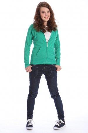 Photo pour Joyeux sourire de jolie adolescente écolière aux longs cheveux bruns, portant un jean bleu foncé et un pull à capuche vert . - image libre de droit