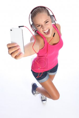Happy sexy teenage girl has music fun with phone