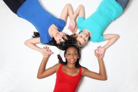 Photo pour Fun star patter par métissé afro-américain, oriental japonais et blond caucasien adolescent écolière fille amis couché sur le sol regarder vers le haut avec gros sm - image libre de droit