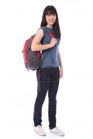 Photo pour Belle jeune adolescente japonaise souriante lycéenne portant un jean bleu et un t-shirt, sac à dos d'école au-dessus de l'épaule . - image libre de droit